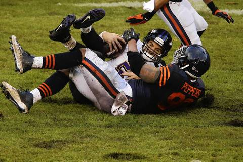 Baltimore Ravens quarterback Joe Flacco (5) is hit by Chicago Bears defensive end Julius Peppers (90).