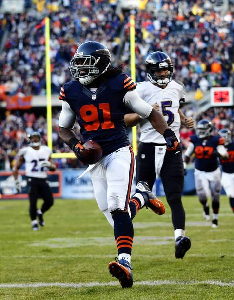 Chicago Bears' David Bass returns interception for a touchdown in 2nd quarter as Baltimore Ravens' Joe Flacco trails the play at Soldier Field.