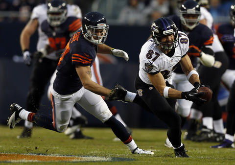 The Ravens' Dallas Clark catches a pass in front of Chris Conte in the 1st quarter.