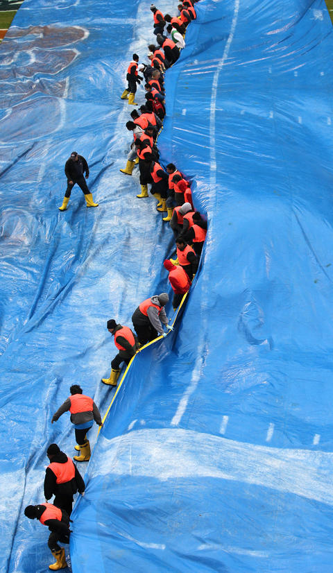 Workers fold up the tarp covering the turf at Soldier Field in Chicago, before the Bears were scheduled to play the Baltimore Ravens. Intense storms are expected to hit the area when the game starts.