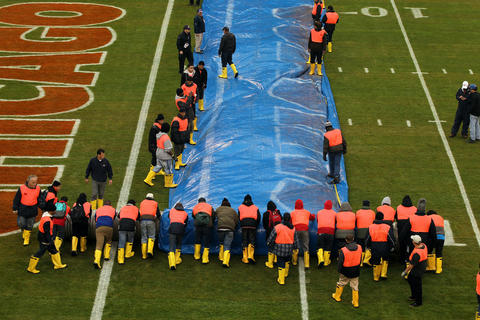 Workers roll up the tarp covering the field before the NFL football game between the Chicago Bears and the Baltimore Ravens on Sunday at Soldier Field in Chicago.