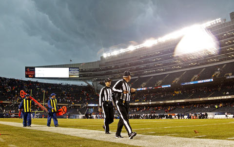 Some of the officials leave the field as the stadium seating area is evacuated.