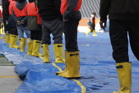 Workers remove the blue tarp from playing surface in preparation of the Chicago Bears game agains the Baltimore Ravens at Soldier Field in Chicago on Sunday.