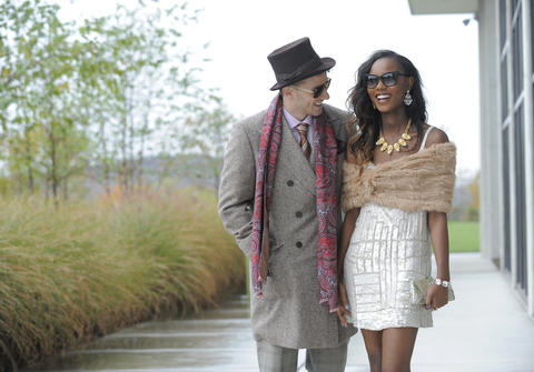 Tim: Reinhart Franc felt hat, $295, Dolce Punta silk tie, $165, V. Barberis suit, $975, wool topcoat, $1,850; pocket circle, $95, and scarf, $250, both by Edward Armah; all from Gian Marco Menswear.  Aniya: Fur stole by 525 America, $245, Parker dress, $389, both from Cupcake; earrings, $98, bracelet, $88, both by Kate Spade from Handbags in the City; Badgley Mischka heels, $225, Sassanova; necklace, $238, Madison Elliott clutch, $375, both from Trillium; Chanel sunglasses, $329, Paris West Optical.