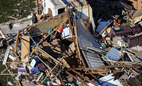 A man gathers belongings from a destroyed house in Washington, Ill.