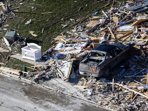 A baby crib sits to the side of destruction in Washington, Ill.