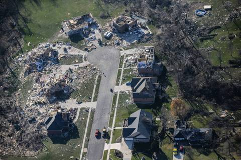 Some houses on one side of a cul-de-sac in Washington, Ill., look untouched while others are demolished.