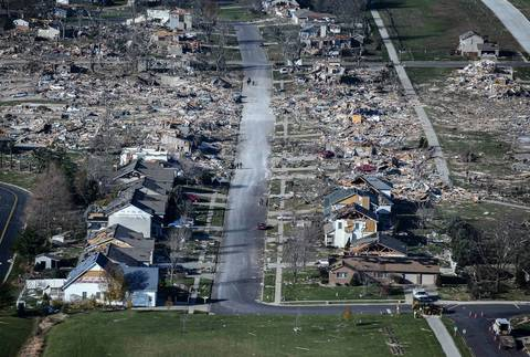 People walk on a clean street surrounded by a path of tornado destruction in Washington, Ill.