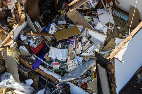 Belongings are piled on the room of a destroyed house in Washington, Ill.