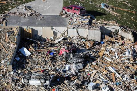 Vehicles are tossed among the debris from the tornado in Washington, Ill.