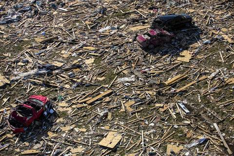 Vehicles sit among the debris in Washington, Ill.