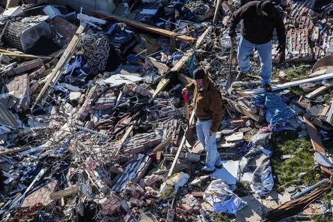 Two men carrying shovels stand in the middle of debris in Washington, Ill.