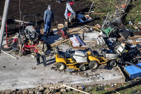 People look at the remains of a garage and it's contents in Washington, Ill.