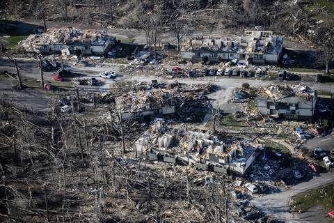 Trees, buildings and cars show the tornado damage in Washington, Ill.