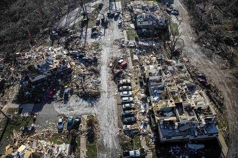 Vehicles are lined up in front of a damaged building in Washington, Ill.