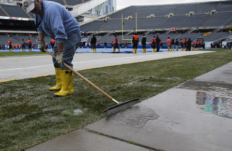 A worker pushes rain water away from the playing surface in preparation of the Chicago Bears game agains the Baltimore Ravens at Soldier Field in Chicago on Sunday.
