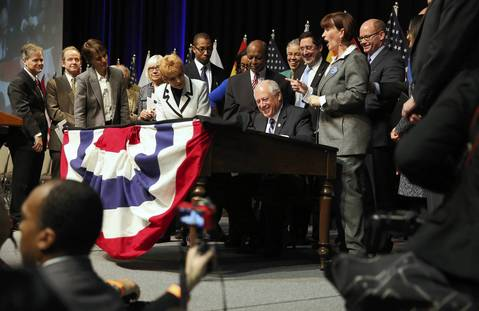On a desk once used by Abraham Lincoln, Illinois Gov. Pat Quinn signs the gay marriage bill at the UIC Forum.
