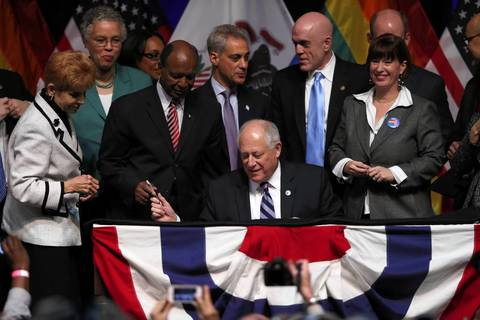 Sitting a desk once used by Abraham Lincoln, Illinois Gov. Pat Quinn signs a bill into law that makes Illinois the 16th state to legalize gay marriage.