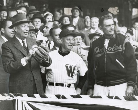 Dwight Eisenhower throws out the first pitch at a 1957 Opening Day game at Washington's Griffith Stadium as managers Chuck Dressen (Washington) and Paul Richards (Orioles) watch.