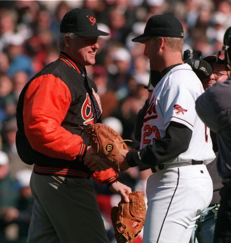 Bill Clinton shakes hands with Orioles catcher Chris Hoiles after throwing the ceremonial first pitch on Opening Day in 1996.