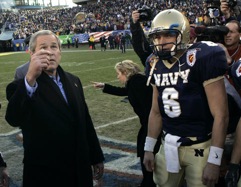 George W. Bush performs the coin toss in front of Navy quarterback Aaron Polanco prior to the 105th Army-Navy football game at Lincoln Financial Field in Philadelphia.