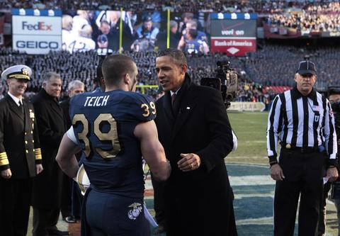 Barack Obama greets Alexander Teich of the Navy football team before the 2011 Army-Navy game in Landover.