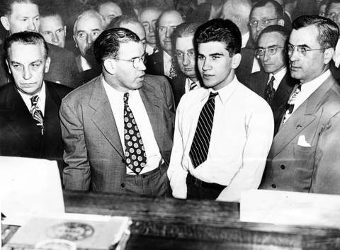 William Heirens, third from left in foreground, is arraigned in July of 1946. Left to right are: State's Attorney William Tuohy, Defense Attorney John Coghlan, Heirens, and Sheriff Michael Mulcahy.