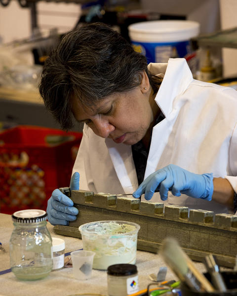 """Conservator Maria Paras works on restoring """"Colleen Moore's Fairy Castle"""" at the Museum of Science and Industry."""