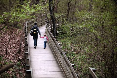 People hike a boardwalk at Starved Rock State Park.