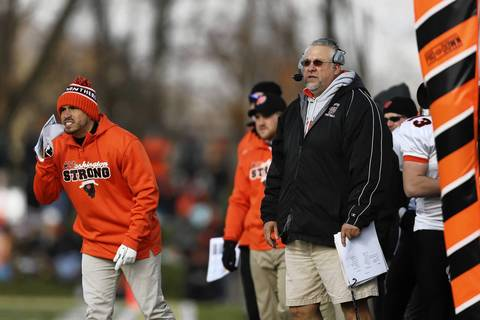 Washington coach Darrell Crouch, right, works from the sideline.