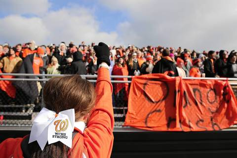 A Washington cheerleader tries to keep the crowd up during the loss to the Sacred Heart-Griffin Cyclones.