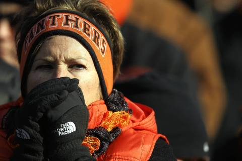 A chilly Washington Panthers fan warms her hands during the chilly game.