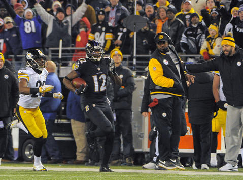 Steelers coach Mike Tomlin, right, hangs close to the sideline as the Ravens' Jacoby Jones runs past on a return in the third quarter.