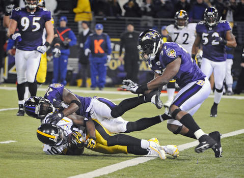 Ravens safety Ed Reed (top) tackles the Steelers' Santonio Holmes (bottom), pushing him back out of the end zone, after Holmes' game-winning touchdown catch with 43 seconds left, which capped a 12-play 92-yard drive that took less than three minutes. The ball was originally ruled to be short of the goal line, but after reviewing the play, officials ruled that it crossed the plane of the end zone. The Steelers won, 13-9, clinching the AFC North title.