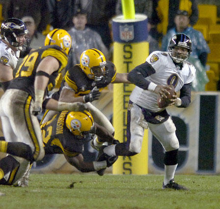Steve McNair is sacked by the Steelers ' James Harrison (bottom) in the second quarter. The Ravens ' 38-7 loss to Pittsburgh was the largest margin of defeat in the nine-year Brian Billick era. McNair had the fewest yards passing in NFL history (63) by a quarterback that completed 13 passes.