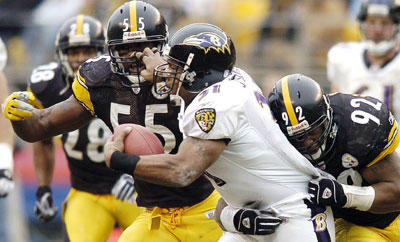 Ravens running back Jamal Lewis is dropped for an 8-yard loss in the second quarter by Steelers defenders James Harrison (92) and Joey Porter . Lewis scored the Ravens' lone touchdown, but was limited to 26 yards on 14 carries.