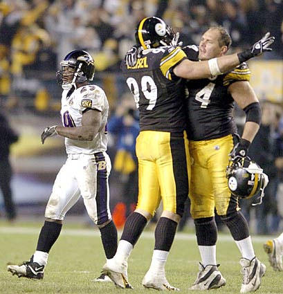 The Steelers ' Brett Keisel (center) and Jeff Hartings celebrate after Chester Taylor (left) dropped a fourth-down pass to end the Ravens' final drive with 20 seconds left. Jeff Reed's 37-yard field goal that split the uprights with 1:36 left in the fourth quarter dashed the Ravens' chances of an unlikely win over their division rival.