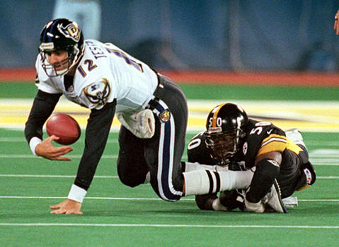 Ravens quarterback Vinny Testaverde (left) is sacked by Steelers linebacker Earl Holmes in the fourth quarter. Testaverde tossed three interceptions in the Ravens' 37-0 loss to the Steelers.