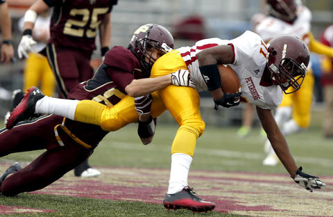 Petersburg's Jordan Noggin is tackled by Poquoson's Mitchell Petain during a game in Poquoson, Virginia on Saturday, November 16, 2013