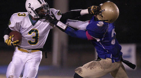 James Green of Smithfield grabs Richard Taylor of Bruton behind the line of scrimmage during the second quarter Friday at Smithfield.