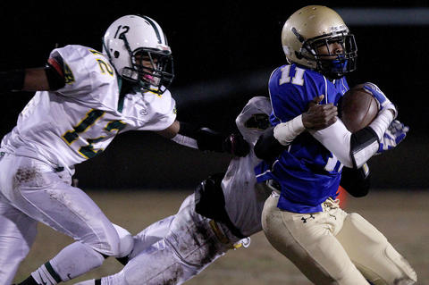 Jamarie Wrenn of Smithfield is stopped by Richard Taylor during the second quarter Friday at Smithfield.