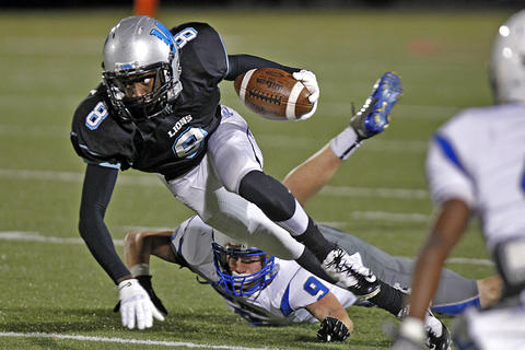 Warhill's Keron Dedmon, center, spins to avoid the tackle of New Kent's Tyler Jenkins, background, during Thursday's game at Wanner Stadium.