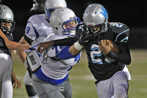 Warhill's Austin Parrott, right, attempts to escape the grasp of New Kent's Wilson Gregory, center, during Thursday's game at Wanner Stadium.