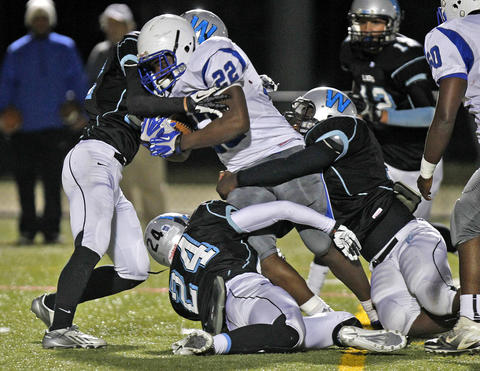 Warhill's Taylor Lyons, left, Bryce Koob, center, and Terrell Blocker, right, attempt to tackle New Kent's Mikel Chalmers, center, during Thursday's game at Wanner Stadium.