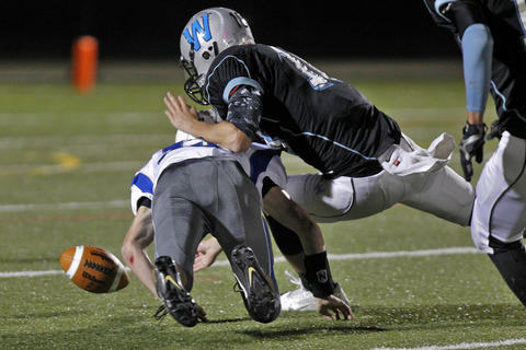 Warhill's Clayton Osterloh, right, dives for the ball after the fumble from New Kent's Zach Ford during Thursday's game at Wanner Stadium.