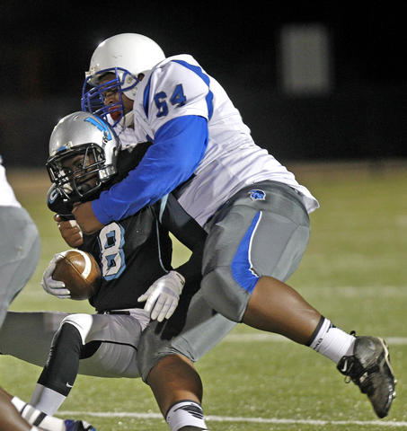 Warhill's Keron Dedmon, left, is brought down by New Kent's Josh Dixon during Thursday's game at Wanner Stadium.