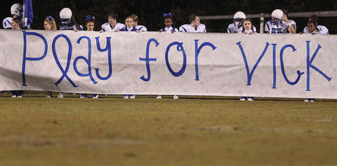 The New Kent football team and cheerleaders pay tribute to Jacob Vick Friday before the game against Bruton.