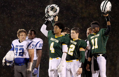 Wilson Gregory (72) of New Kent turns his head as Kapri Doucet (4) Kyle Mackem (52) and Bilal Wallace (11) of Bruton raise their helmets in salute to Jacob Vick Friday at Bruton. Vick passed away after collapsing at practice Tuesday.