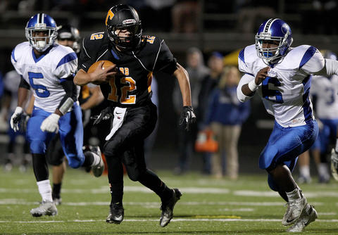 Nicholas Hunter of Tabb tries to scramble away from Malcolm Reynolds of York during the first quarter Friday at Bailey Field.