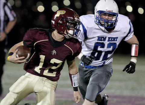 Poquoson quarterback Johnny Pryce gets away from John Elswick of New Kent to scramble for a touchdown during the second quarter Thursday at Poquoson.